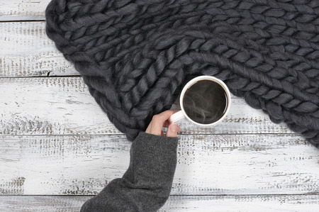 Woman hand in warm sweater holding cup of hot coffee near super chunky woven blanket. Top view point.