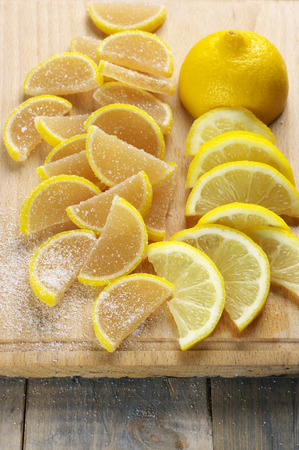 segmento: Pile of lemon segment shaped candied fruit jelly and sliced lemon on wooden cutting board. Foto de archivo