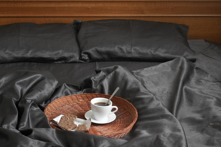 bedhead: Cup of coffee and milk chocolate on wicker tray in bed with black satin linen and wooden bedhead.