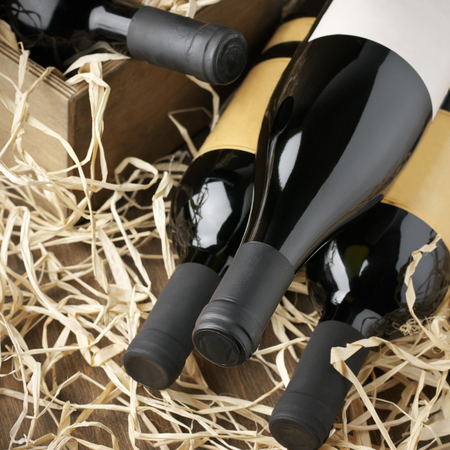 haulm: Assorted closed wine bottles lying on straw and vintage wooden box.