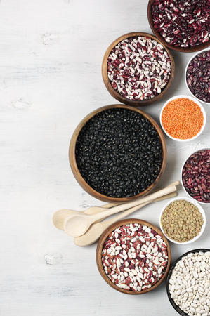 vigna: Set of various beans in bowls: white, black, purple and red speckled beans, red and green lentils. White wooden background, top view. Stock Photo
