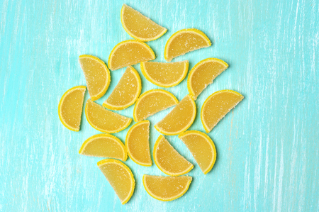 sweetstuff: Lemon segment shaped candied fruit jelly on turquoise colored wooden background. Top view point.