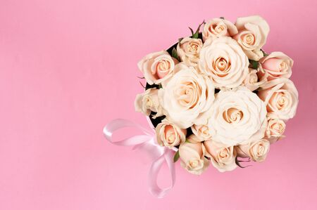 pink satin: Bunch of delicate pastel colored roses in gift box with satin bow on pink background. Top view. Stock Photo