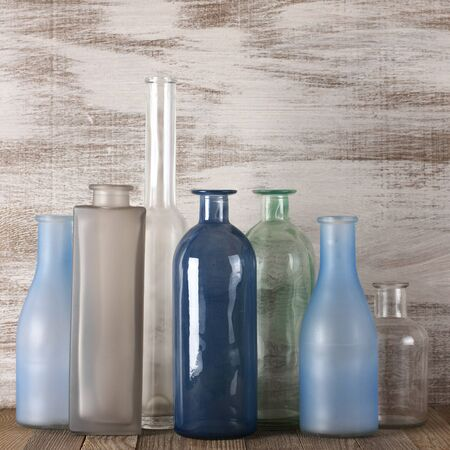 muted: Set of various muted colored glass bottles against rustic shabby wooden wall.