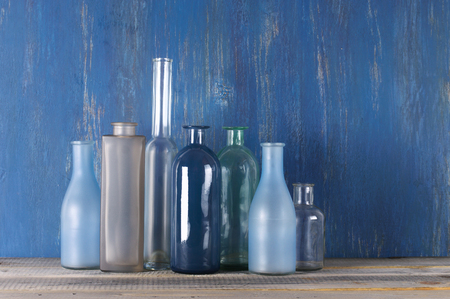 muted: Set of various muted colored glass bottles against blue shabby wooden wall.