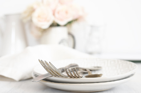 Vintage silverware set on plates against roses bouquet at background. Light pastel colored image. Soft focus, shallow DOF, focus on top of forks. Stock Photo