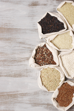 Set of various rice in canvas bugs on wooden background: white glutinous, black, basmati, brown and thai red mixed rice. Top view. Stock Photo