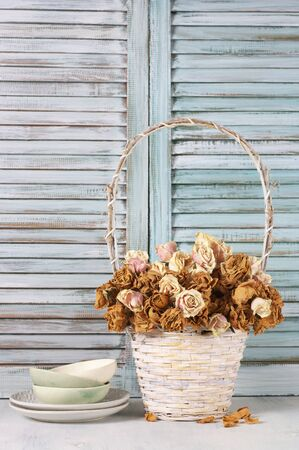 Dried roses in white wicker basket and crockery against wooden blinds. Shabby chic interior decor. Stock Photo