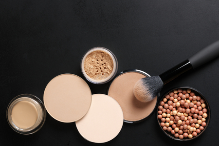 applicator: Cosmetic set of various shades compact and loose face powder, bronzed pearls, concealer and makeup brush on black background. Top view point, flat lay.