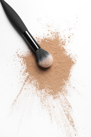 Scattered tan colored facial loose powder and make-up brush isolated on white background. Top view point. Stock Photo