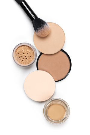 Cosmetic set of various shades compact and loose face powder and makeup brush on white background. Top view point, flat lay.