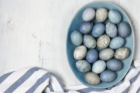 Muted blue and grey Easter eggs in handmade ceramic dish with towel on rustic white wooden background. Top view point.