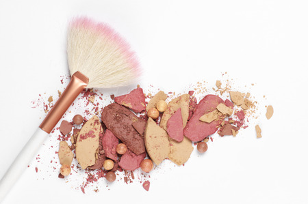 Heap of various crashed face powder, blushers, eyeshadow and brush on white background. Neutral colored makeup products. Top view point. Stock Photo