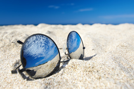 Round sunglasses with mirror reflection of sky in white sand on sunny summer beach.  Stock Photo