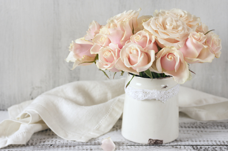 Bouquet of delicate pink roses in vintage tin vase on white rustic wooden background. Shabby chic home decor. Stock Photo