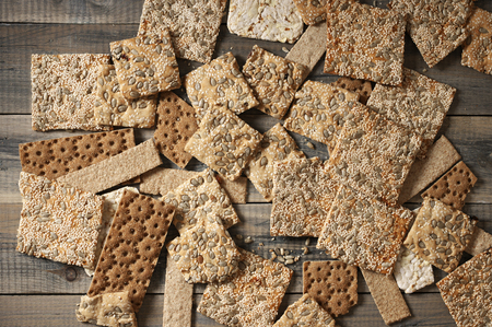 sesame cracker: Various crispy wheat, rye and corn flatbread crackers with sesame and sunflower seeds on rustic grey wooden background. Top view point.