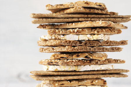 Stack of various crispy wheat, rye and corn flatbread crackers with sesame and sunflower seeds on white wooden background. Фото со стока - 75967362