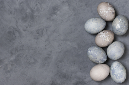 Natural dyed grey Easter eggs on dark gray background. Top view point.