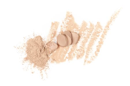 Smudged and broken makeup concealer and pile of loose face powder isolated on white background. Top view point.