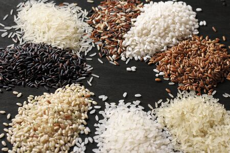 multiple: Piles of various rice on black wooden background: white glutinous, black, basmati, brown and thai red mixed rice. Shallow DOF.