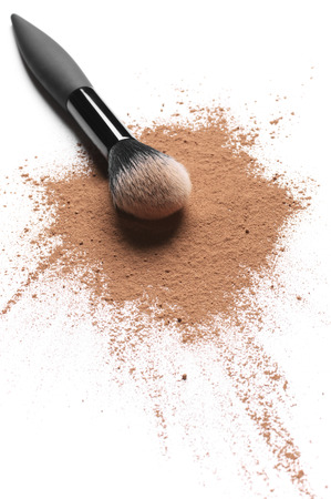 Scattered tan colored facial loose powder and make-up brush isolated on white background. Stock Photo