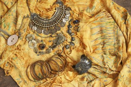 Bohemian chic bronze jewelry set on yellow ethnic batik dress. Boho outfit. Top view point.