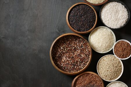 Set of various rice in bowls: white glutinous, black, basmati, brown and thai red mixed rice. Black wooden background, low light, top view.