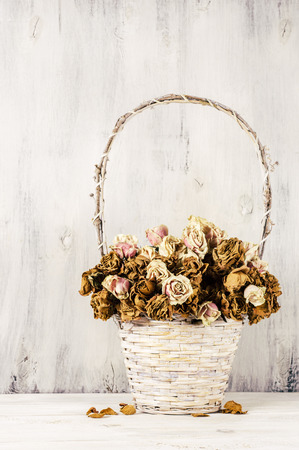 Dried roses in wicker basket on rustic white wood background. Shabby chic interior decor. Filtered image.