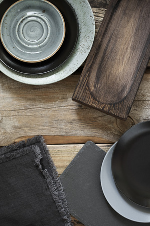 Grey kitchen utensils on rough distressed wooden table: crockery, silverware, oak cutting board, slate trays and linen towels. Top view point.