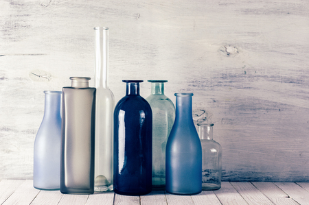 Set of various muted colored glass bottles against white shabby wooden wall . Filtered toned image. Stock Photo