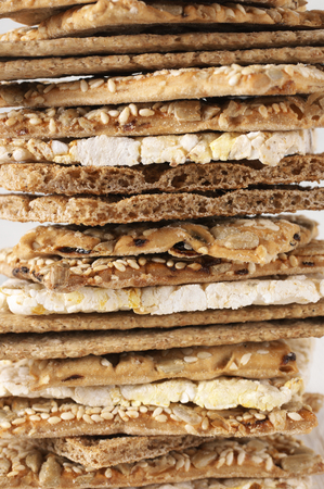 sesame cracker: Stack of various crispy wheat, rye and corn flatbread crackers with sesame and sunflower seeds close-up. Shallow DOF. Stock Photo