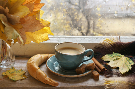 Cozy autumn still life: cup of coffee with croissant and cinnamon, bouquet of fall leaves and warm blanket on vintage wooden windowsill against rainy weather from outside.