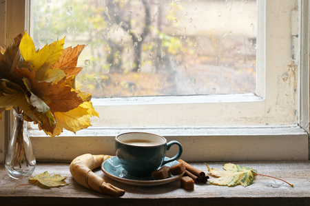 Cozy autumn still life: cup of coffee with croissant and cinnamon near bouquet of fall leaves on vintage wooden windowsill against rainy weather from outside. Stock Photo