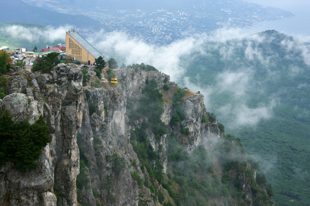 ropeway: Cable way station on steep cliff in fog. Ai-Petri, Crimea. Stock Photo