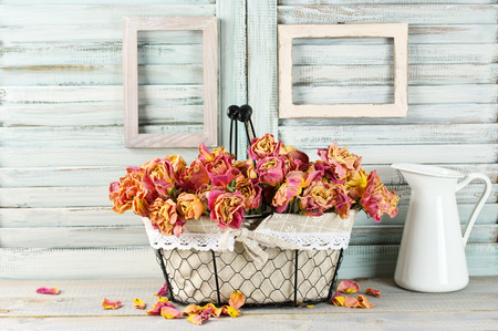 Nature morte shabby chic: bouquet de roses roses sèches vintage dans un panier métallique et pichet contre des stores en bois blanc avec cadres photo vides. Banque d'images