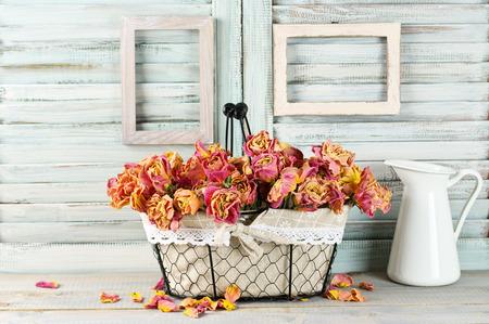 Shabby chic stilleven: bos van vintage roze droge rozen in mand en kruik tegen witte houten jaloezieën met lege fotolijsten. Stockfoto