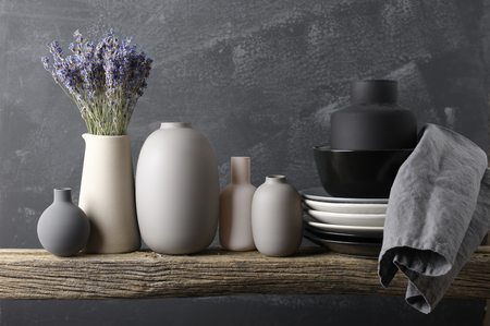 Home decor - neutral colored vases with lavender bouquet, dishware and linen napkin on rough distressed wooden shelf against grey wall.