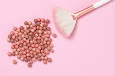 Mixed pink and tan colored glow face pearls blush and brush on pink background. Top view point.