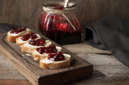 Sandwiches with butter and cranberry jam on wooden cutting board  and glass jar with confiture.