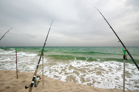 Fishing rods on sandy sea shore at end of earth. Moody overcast weather.