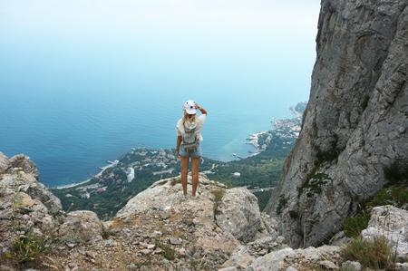曇りの天候で海と山の頂上に立っている若い女性。背面図。 写真素材