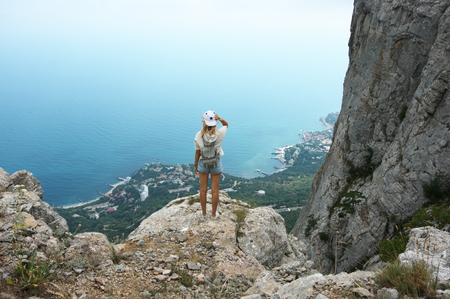 Young woman standing on top of mountain against sea at cloudy weather. Back view. Standard-Bild