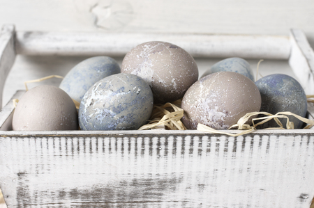Natural dyed grey Easter eggs close-up in shabby white box with straw. Banque d'images