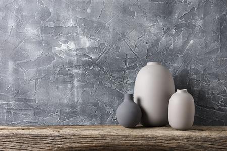 荒い石膏灰色の壁に対して苦しんだ木製の棚に中立色の花瓶。ホームインテリア。 写真素材 - 93124711