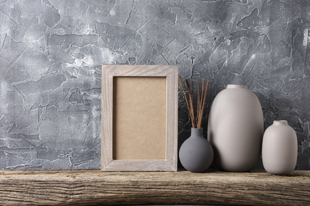 Neutral colored vases and shabby photoframe on distressed wooden shelf against rough plaster grey wall. Home decor.