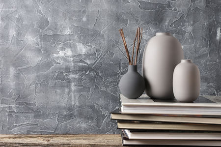 Neutral colored vases and stack of books on distressed wooden shelf against rough plaster grey wall. Home decor.