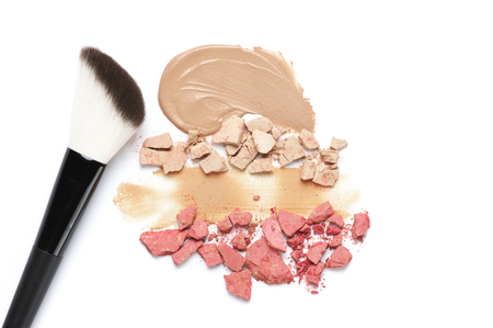 Heap of crashed face powder, blushers, smudged concealer and brush on white background. Neutral colored makeup products. Top view point. Stock Photo