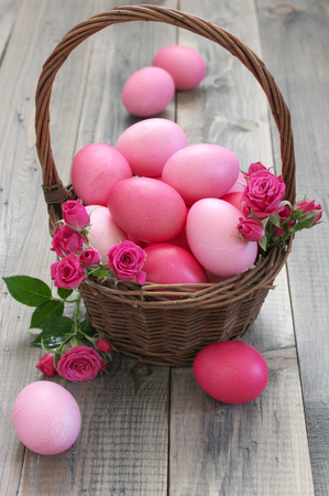 Varicolored pink Easter eggs in wicker basket with roses decor on rustic grey wooden background.