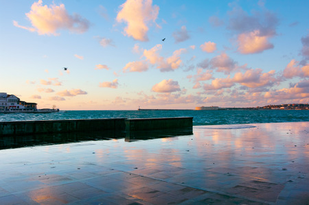 Wet granite seafront with reflection of pink clouds at sunset. Sevastopol, Crimea.