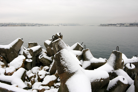Winter seascape with snowy breakwater against hazy town at cold moody weather.
